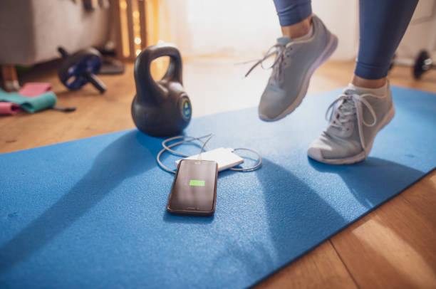 Woman exercising on yoga mat with smart phone and power bank stock photo