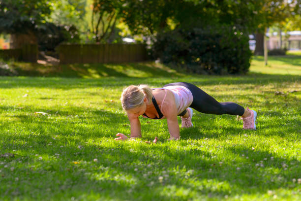 Woman exercising plank on forearms in the park stock photo