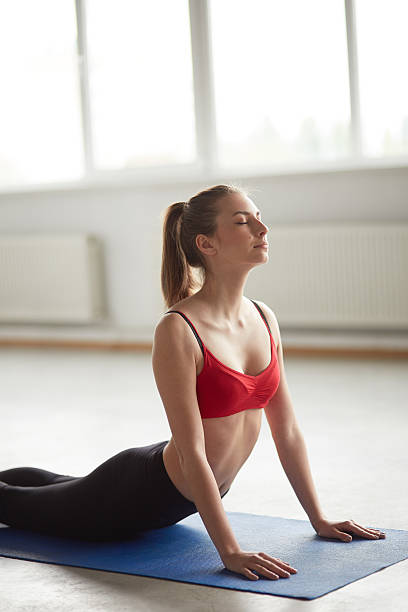 woman exercising sun salutation cobra pose yoga Vertical portrait of one woman exercising sun salutation cobra pose yoga posture in studio with big windows and natural light. Girl doing aerobic exercise for back pain relief cobra pose stock pictures, royalty-free photos & images