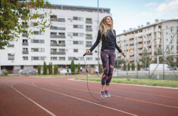 Woman exercising with a jump rope stock photo