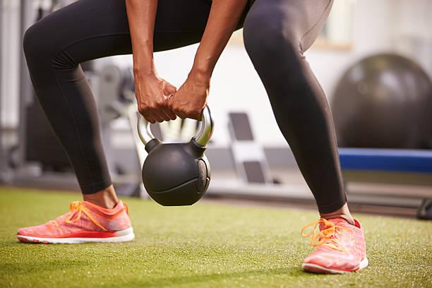 mulher se exercitando com kettlebell peso, baixa-corte de seção - parte inferior - fotografias e filmes do acervo