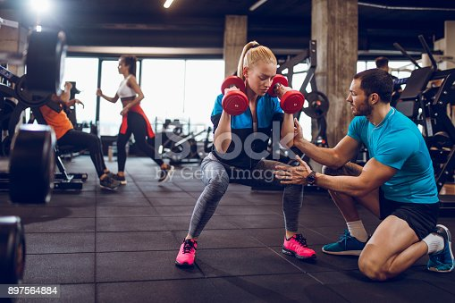 istock Woman exercising with dumbbells in squat position 897564884
