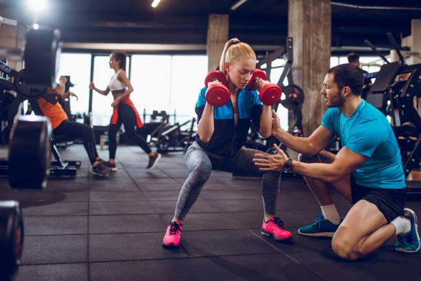 mujer haciendo ejercicio con mancuernas en posición de cuclillas - entrenador personal fotografías e imágenes de stock