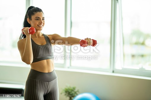 1035512048istockphoto Woman exercising with dumbbells 1195776297