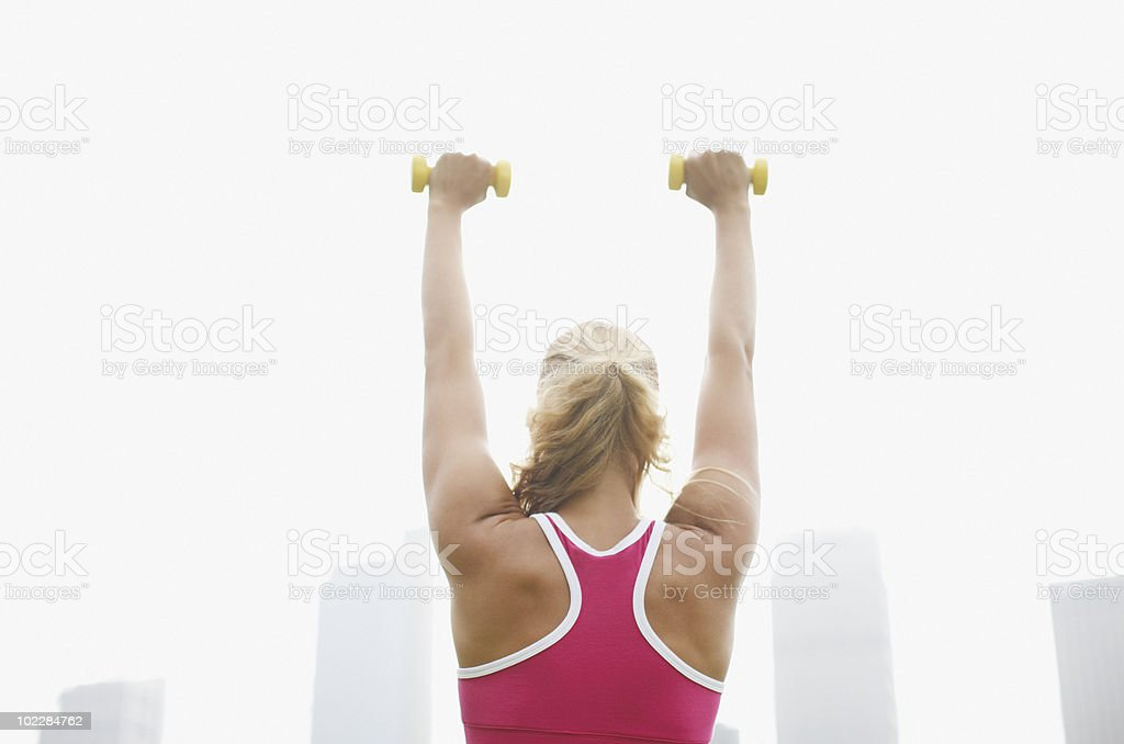 Woman exercising with hand weights in park stock photo