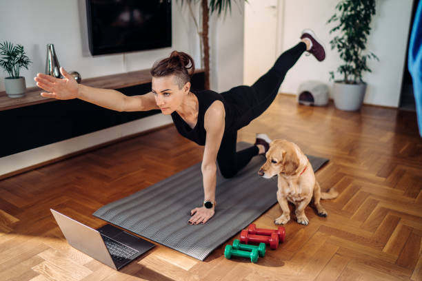 woman exercising with her dog in the living room stock photo
