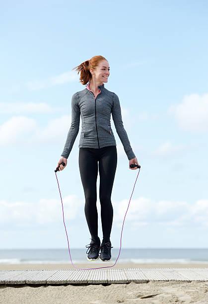 frau training mit dem springseil im freien - leinenhosen frauen stock-fotos und bilder