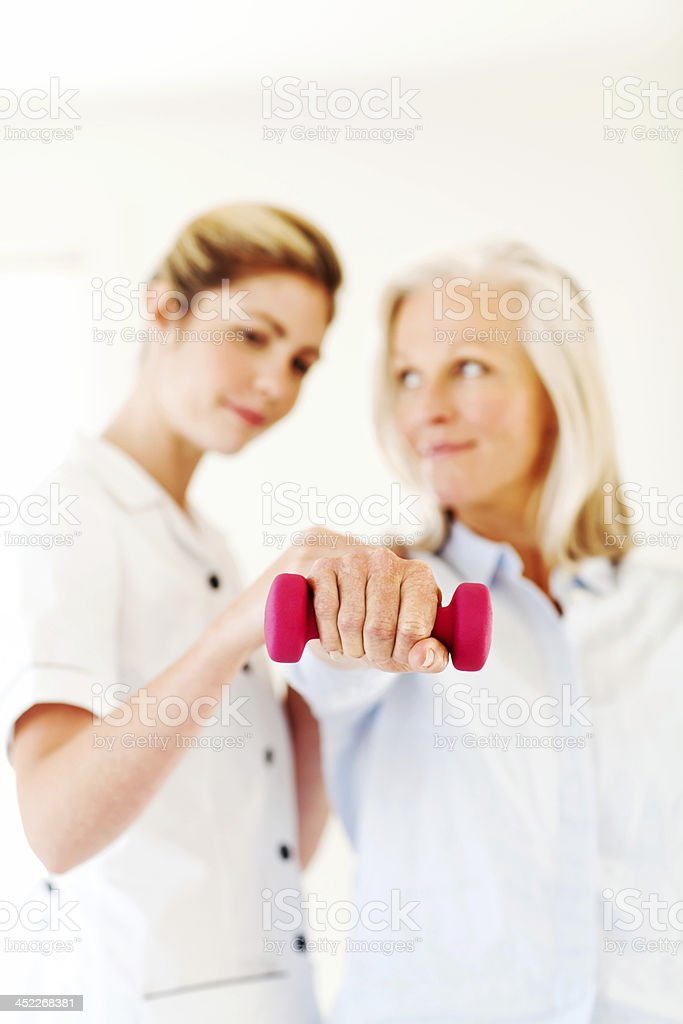 Woman Exercising With Occupational Therapist stock photo