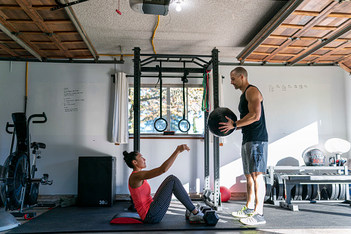 Beautiful and fit Pacific Islander woman and muscular Caucasian man doing an abdominal strength workout with a weighted ball in a home gym set up in the garage of their home.