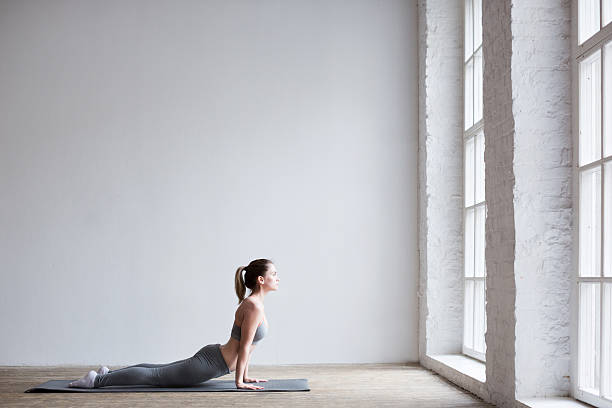 Woman exercising yoga indoors. stock photo