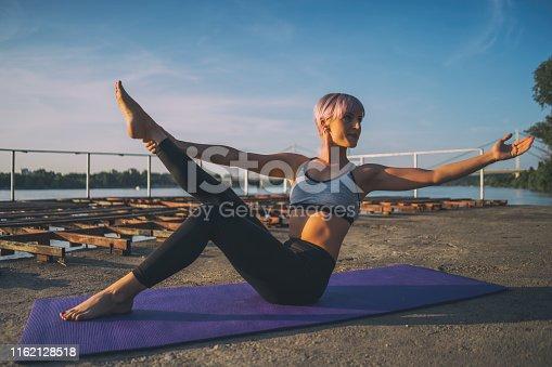 Woman practicing yoga on sunny day. Padangusthasana, Hand to big toe pose