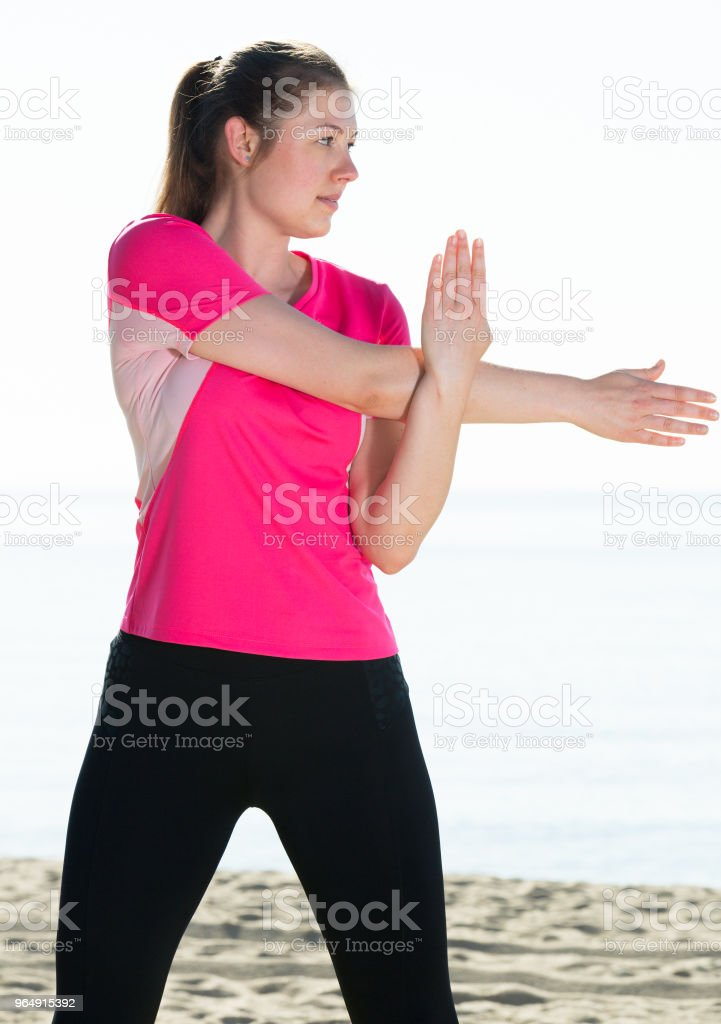 Woman exercising yoga poses on beach royalty-free stock photo