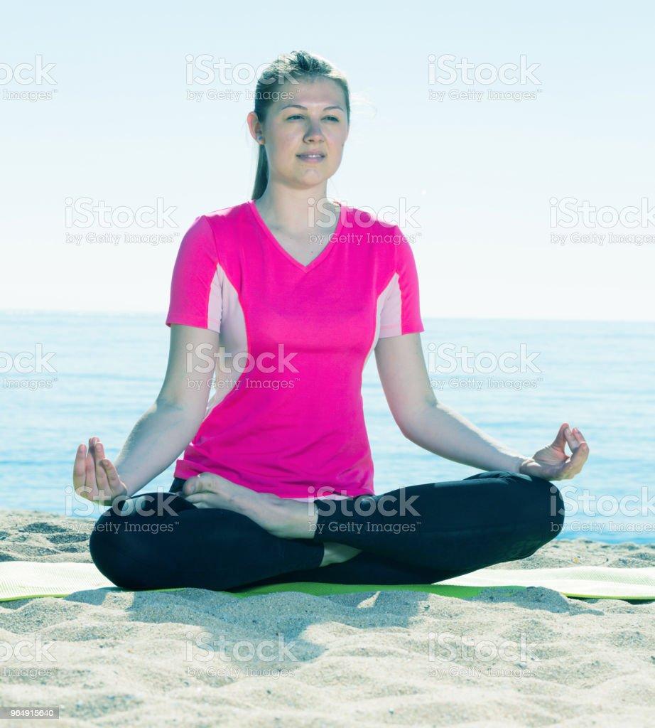 Woman exercising yoga poses on beach royalty-free stock photo