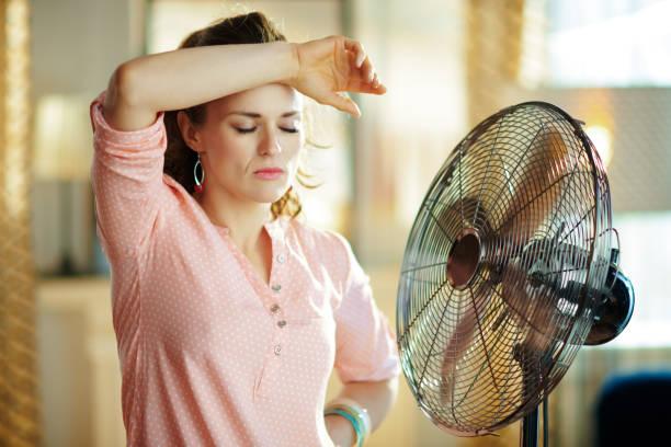 kvinna utmattad från sommar värmen medan man står framför fläkten - kvinna ventilationssystem bildbanksfoton och bilder