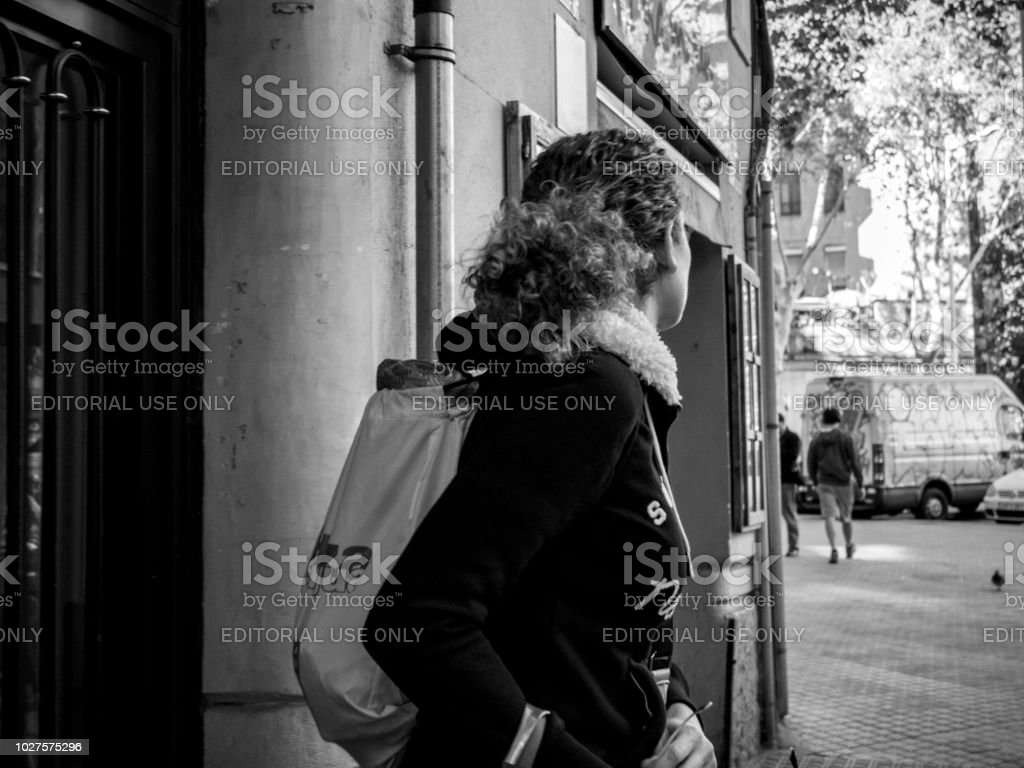 Woman exiting house door wearing backpack stock photo