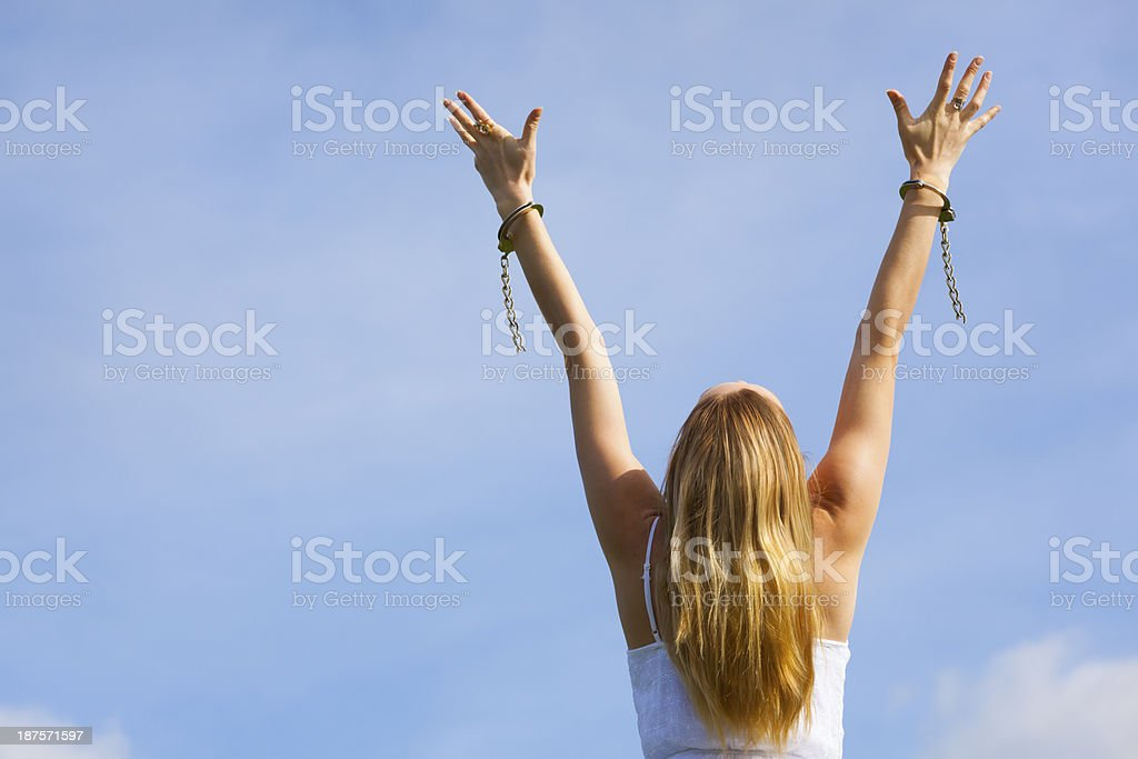 Woman experiencing freedom from handcuffs stock photo