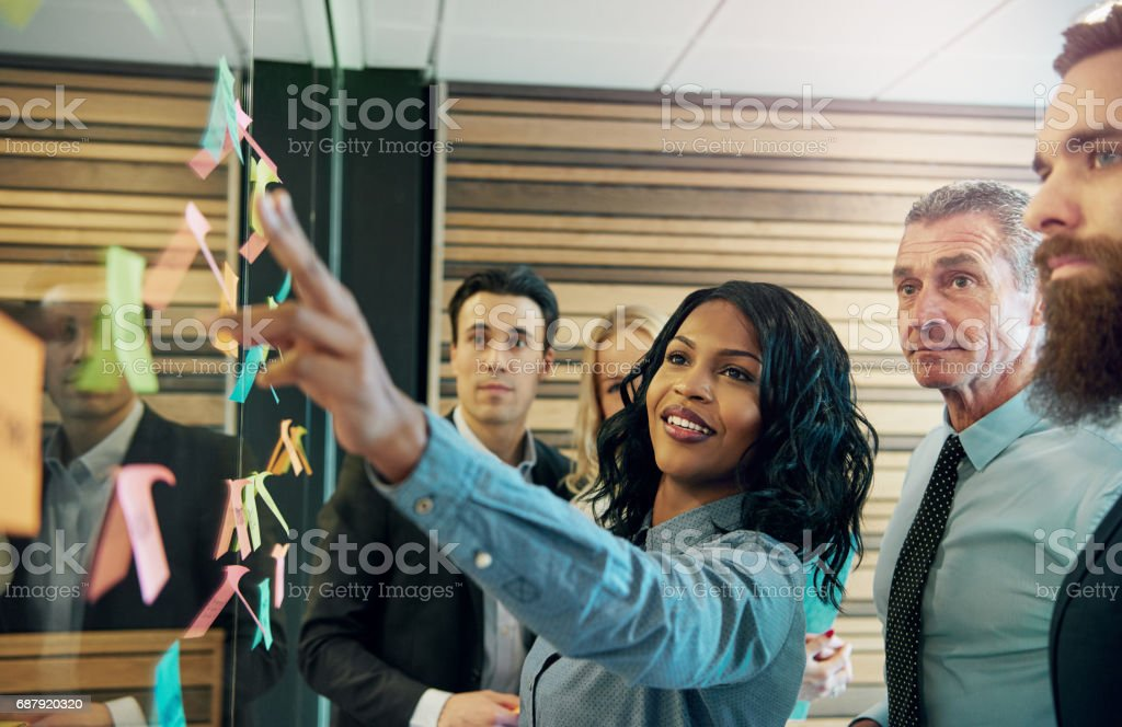 Woman explaining the plan to office team stock photo