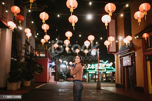 A Caucasian woman walks the streets of Chinatown in L.A. California on a warm evening, exploring the cities night life.  Bright traditional lanterns illuminate the scene.