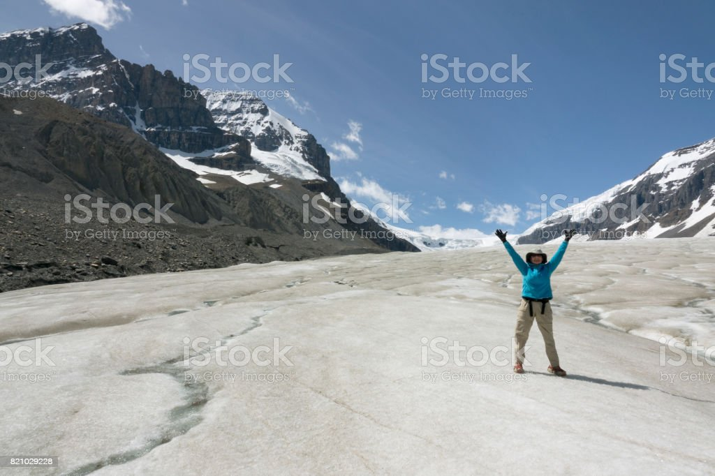 Woman explores hikes melting Athabasca Glacier Jasper National Park Alberta Canada stock photo