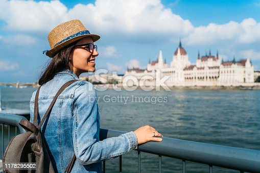 Young Caucasian woman exploring Budapest. Hungarian Parliament Building across the river.