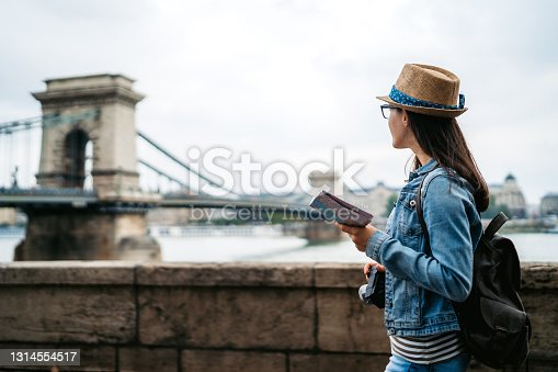 Young caucasian woman exploring Budapest with a map. Széchenyi Chain Bridge in background.
