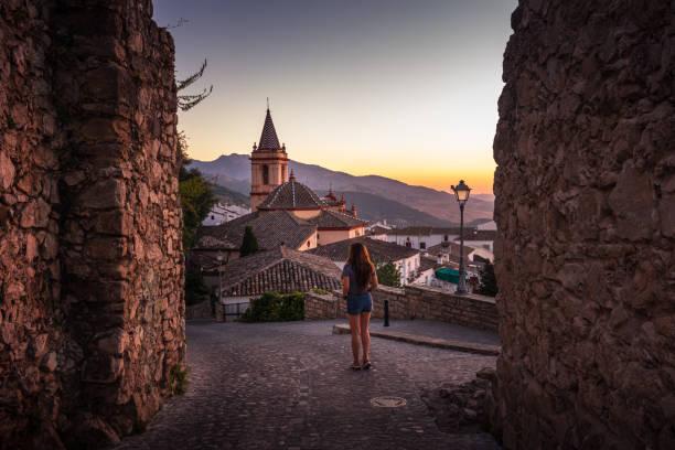 Woman exploring cobblestone streets of Zahara de la Sierra in Spain at sunset stock photo