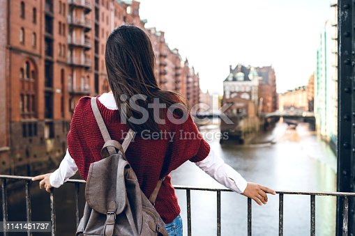 Young tourist woman is exploring Speicherstadt, old part of Hamburg, Germany