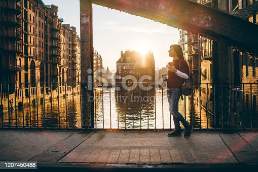 Young tourist woman is exploring Speicherstadt, old part of Hamburg, Germany.