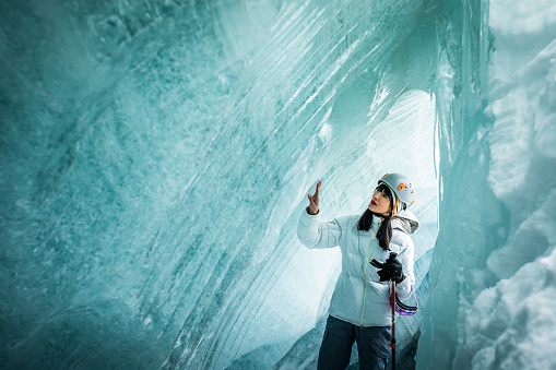 Female explorer wearing ski gear and helmet touching ice in glacial cave.