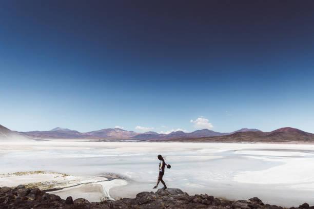Woman exploring salt flat and volcanic landscape in Atacama desert stock photo