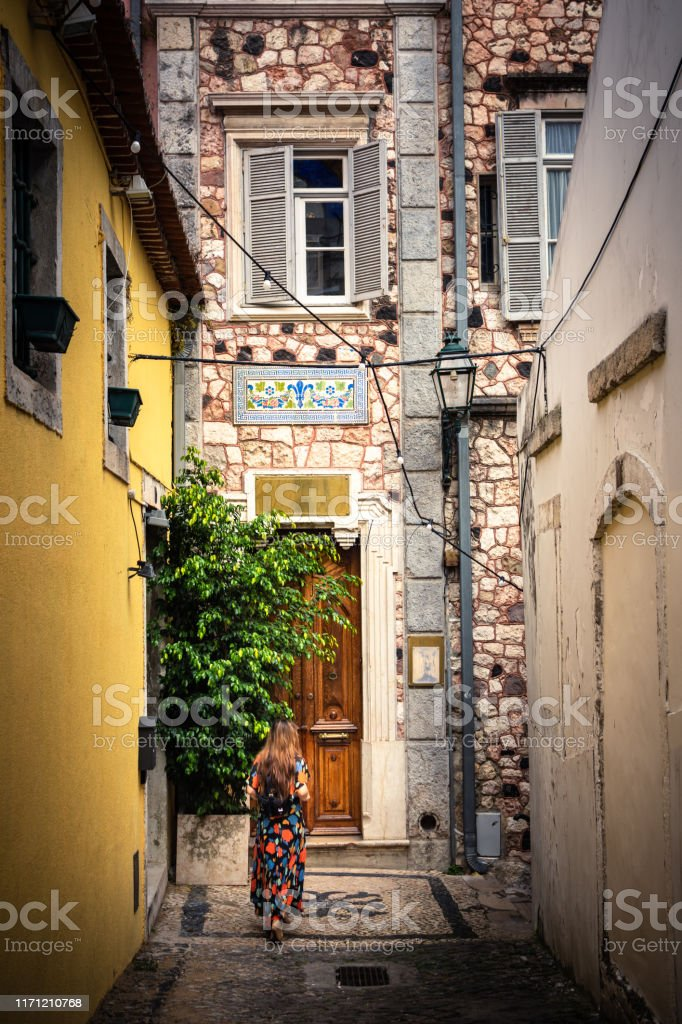 Woman exploring the alleys of the Alfama District in Lisbon, Portugal - Royalty-free Adult Stock Photo