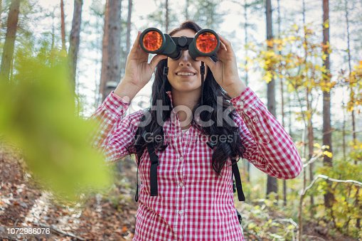 Attractive female explorer looking through the binocular