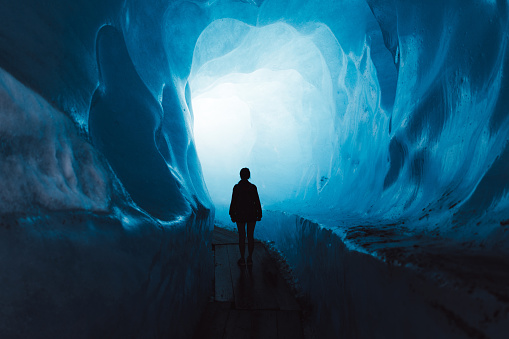 Woman exploring the world of a big glacier inside the ice cave in Switzerland