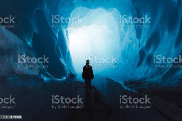 Photo of Woman exploring the world of a big glacier inside the ice cave in Switzerland
