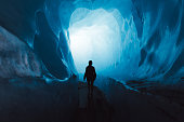 Silhouette of woman tourist walking inside the beautiful turquoise colored ice cave inside of Rhone glacier in Swiss Alps