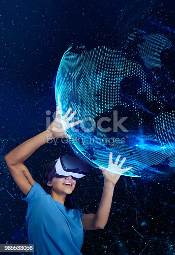 istock Woman exploring virtual reality. Holding holographic earth model 965533056
