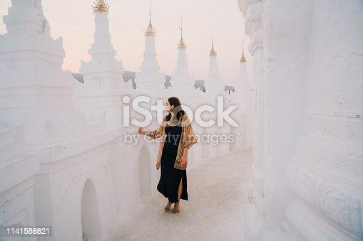 Young Caucasian women exploring white Hsinbyume Pagoda in Mandalay