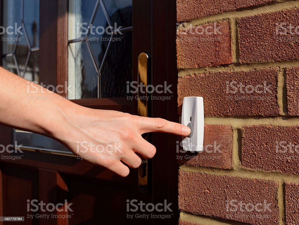 Woman extends her hand to ring doorbell stock photo