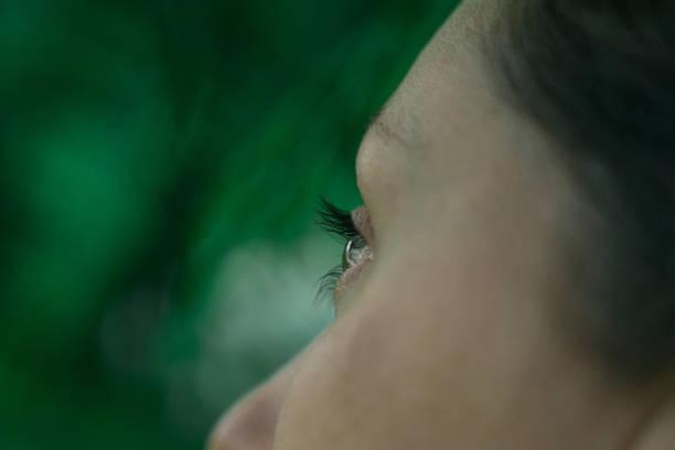 Mujer ojo primer plano sobre el fondo verde - foto de stock
