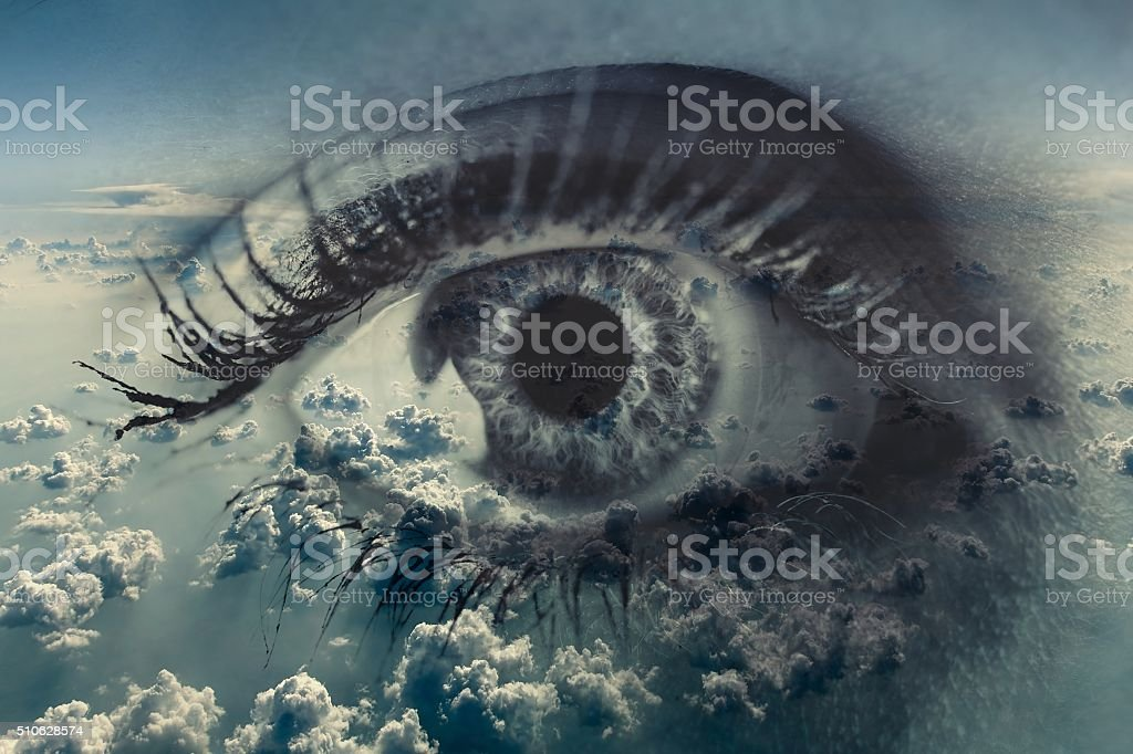 Woman eye on the background of clouds. stock photo