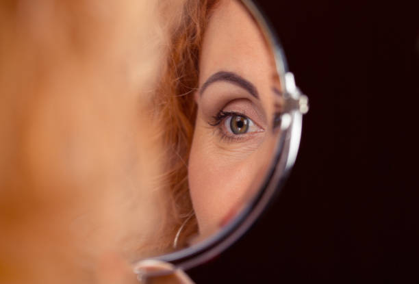 woman eye reflected in a round small mirror. - eyelid stock pictures, royalty-free photos & images