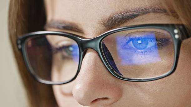 Woman Eyes with Glasses Close-up shot of woman eyes in glasses reflecting a working computer blue screen alternative pose stock pictures, royalty-free photos & images