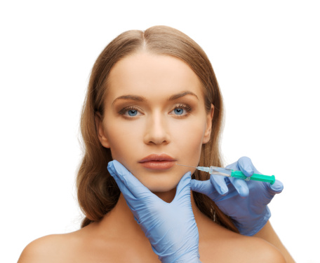 istock woman face and beautician hands with syringe 183155412