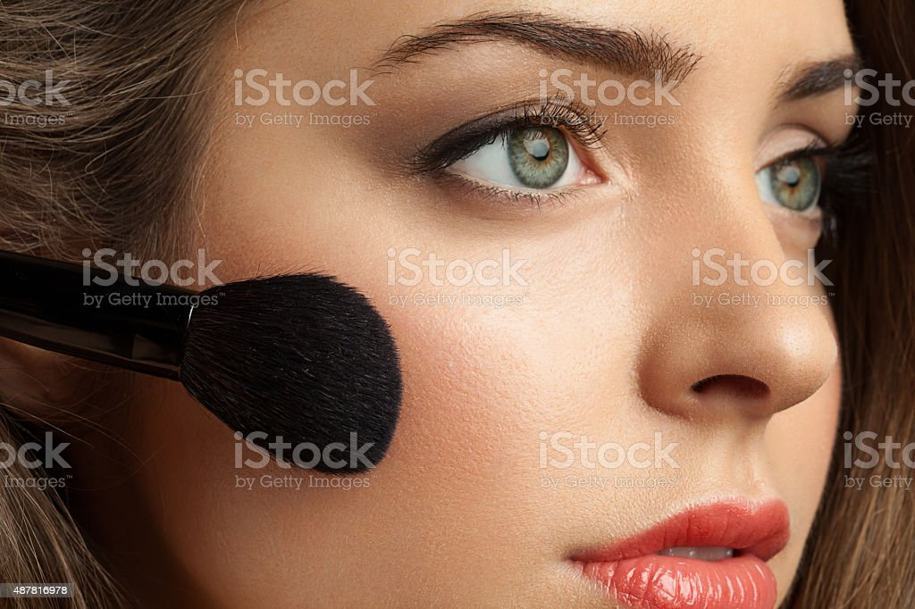 Woman face powders, and apply blush to the cheekbones stock photo