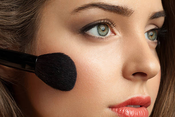 Woman face powders, and apply blush to the cheekbones Beautiful woman face powders, and apply blush to the cheekbones blusher make up stock pictures, royalty-free photos & images