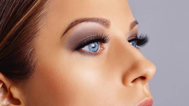 Woman face with long eyelashes and smokey eyes make-up stock photo