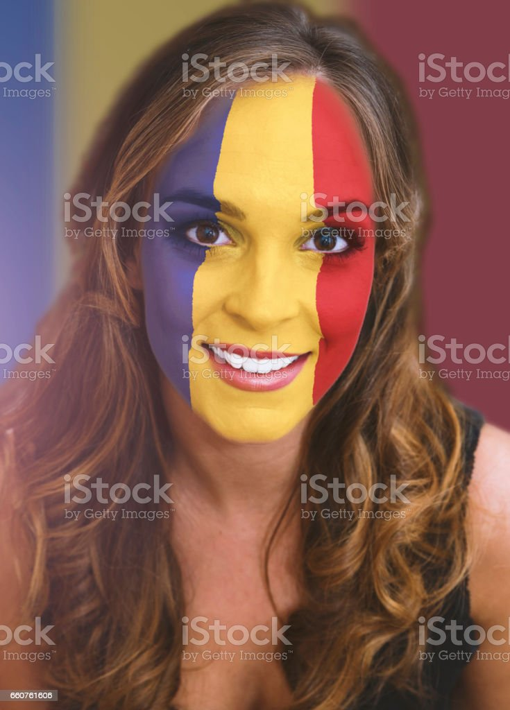 Woman face with painted flag of Romania stock photo
