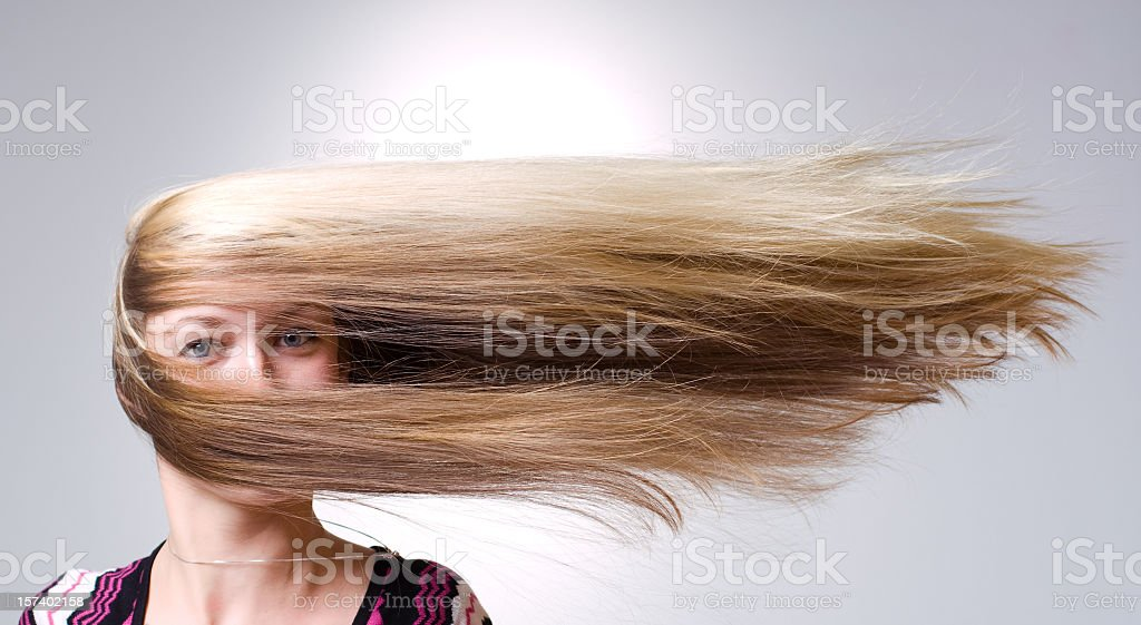 Woman facing straight ahead with hair being blown aside stock photo