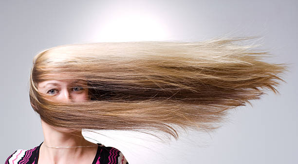 woman facing straight ahead with hair being blown aside - blowing stock photos and pictures