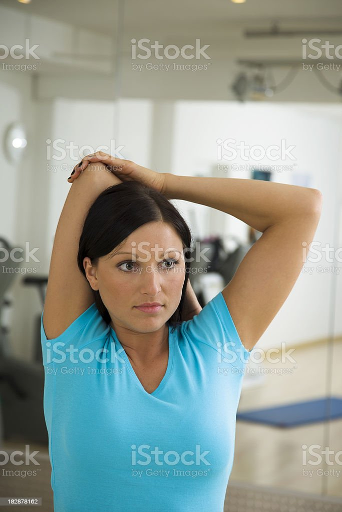 Woman Facing the Camera Doing Triceps Stretch stock photo
